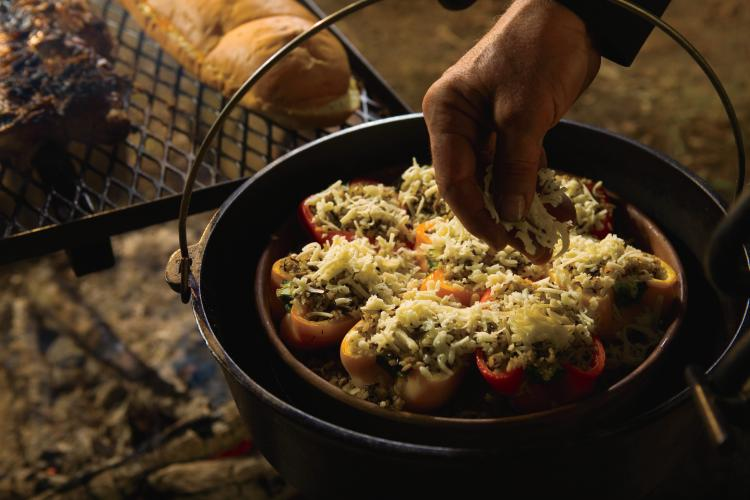 Stuffed peppers cook over an open campfire